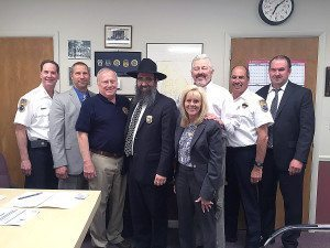 Chabad's Rabbi Shalom Paltiel has been appointed Chaplain of the Port Washington Police District. He is pictured with the chiefs and commissioners, being presented with his official shield. From left: Chief James Salerno, Deputy Chief Jeffrey Morris, Commissioner James Duncan, Rabbi Paltiel, Commissioner Angela Lawlor-Mullins, Commissioner Dave Franklin, Deputy Chief Robert Del Muro and Police District Attorney Rich Finkel