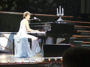 In a gown with a long train she designed and made herself, Feuss performs à la Liberace at the 2006 Senior Ms. America Contest in Las Vegas. Previously, she  was first runner-up in the Senior Ms. New York Contest and was invited to play  and sing at the finals in Las Vegas.