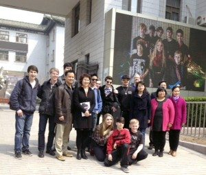 In front of a billboard advertising the band, iSchool band members with Ken Benshish and Yi Qian, owners of The iSchool of Music & Art, and some of the tour group's Chinese hosts