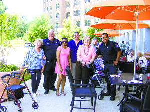 Port Washington First Responder and EMT enjoy a photo opportunity with residents of The Amsterdam at Harborside during the barbecue.