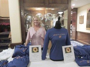 """Christa Egan selling T-shirts with the slogan """"Always in our hearts."""""""