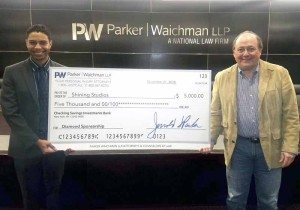 Kyle Savage of Shining Studios receives a check for $5,000 from Jerrold Parker of Parker Waichman, LLP.